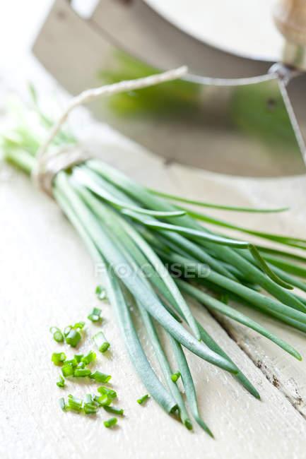 Rodajas de cebollín verde, manojo de cebollino crudo - foto de stock