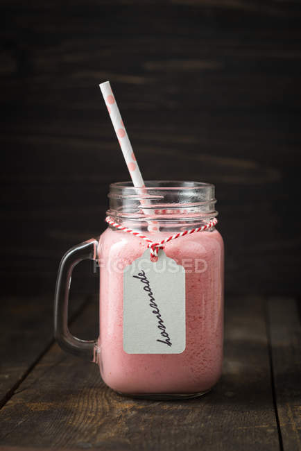 Pink milk shake in glass ware with straw isolated on black background — Stock Photo