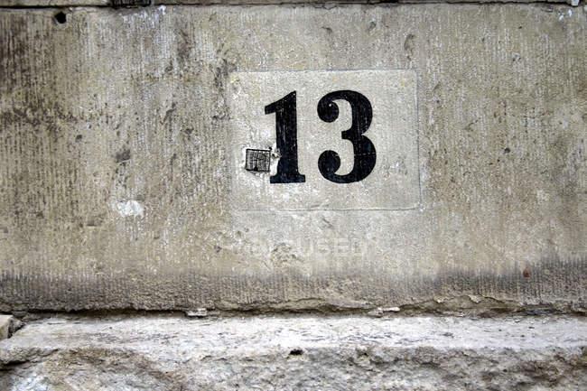 Numéro 13 sur le mur de béton gris vieux sale — Photo de stock