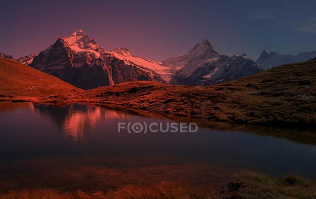 Coucher de soleil et lac dans les montagnes, Alpes suisses — Photo de stock