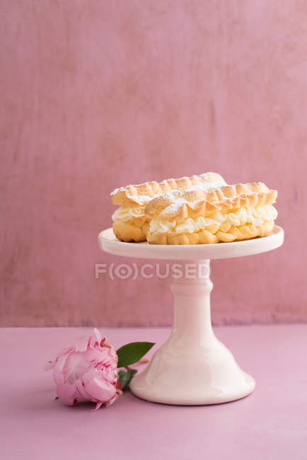Eclairs on cake table and peony flowers on table — Stock Photo