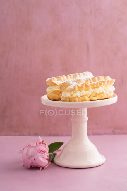 Эклеры на торт стол и пион цветы на столе — стоковое фото