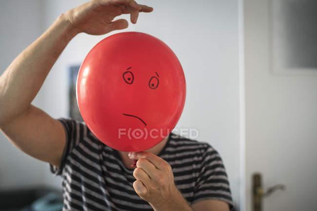 Homem, cobrindo o rosto com balão vermelho com emoção triste cara pintada — Fotografia de Stock