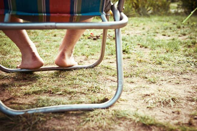 Immagine ritagliata di gambe a piedi nudi, uomo seduto sulla sedia a sdraio — Foto stock