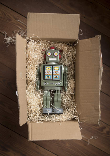 Retro robot in cardboard box, top view — Stock Photo
