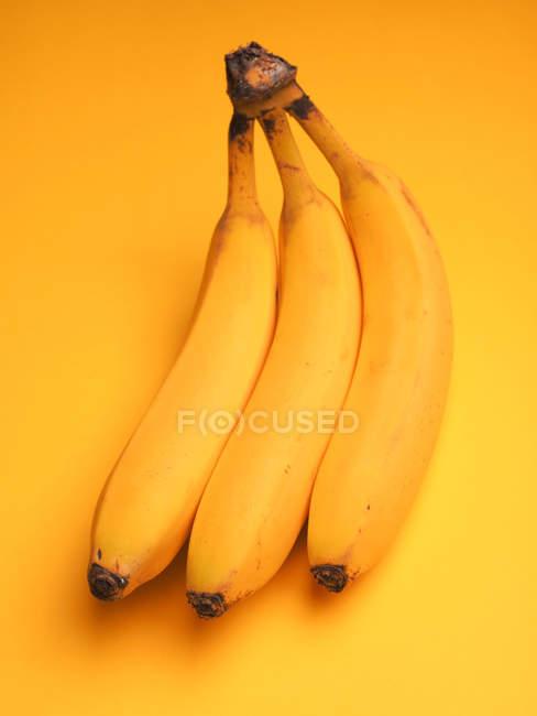 Plátanos amarillos aislados sobre fondo amarillo - foto de stock