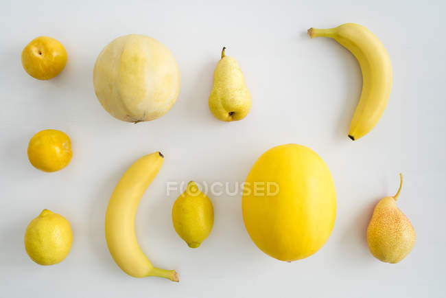 Frutas amarelas na superfície branca, melões, peras, limões e bananas — Fotografia de Stock