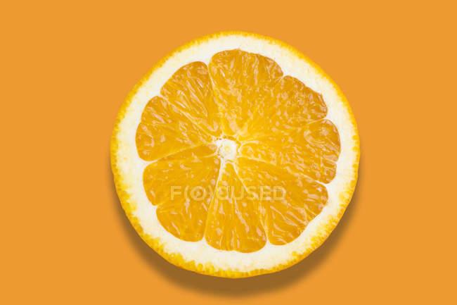 Rodaja de naranja aislada sobre fondo naranja - foto de stock