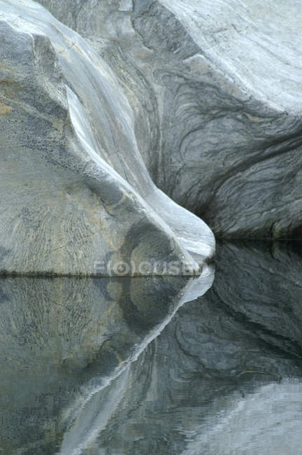 Grey rock wall reflection in water surface — Stock Photo