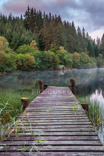Molo di legno al lago in montagna — Foto stock