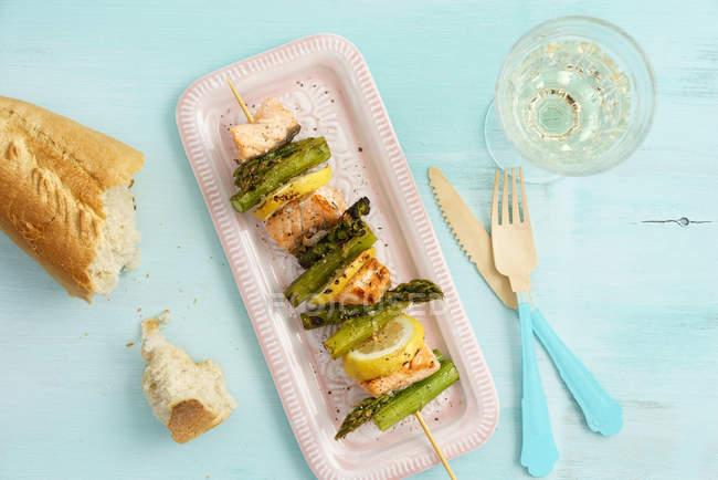 Sulcado espargos com salmão no prato e rodelas de limão — Fotografia de Stock