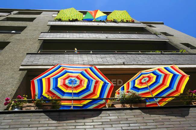 Casa residencial con balcones y paraguas de colores verano - foto de stock
