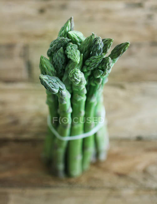 Green asparagus heap on wooden table — Stock Photo