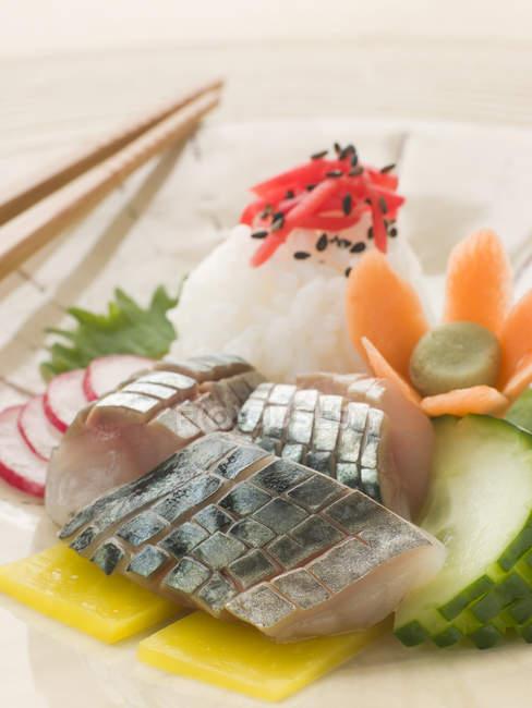 Sashimi de caballa cruda decorado con pepino y zanahoria cruda - foto de stock