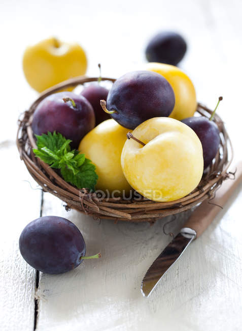 Purple and yellow plums on wooden basket bowl, table with knife — Stock Photo