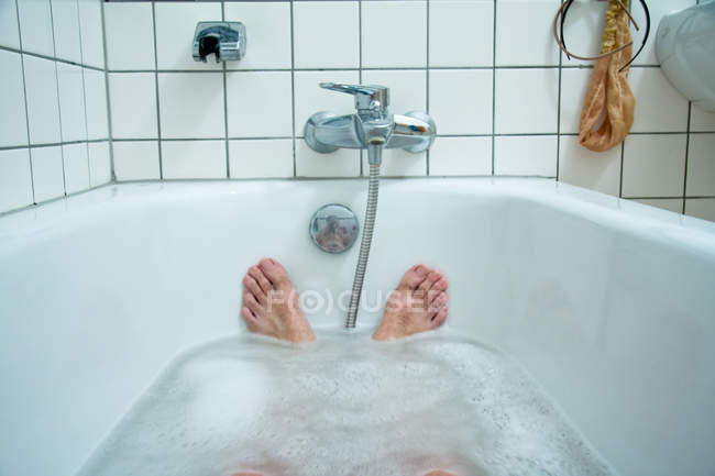 Perspective shot of person lying relaxing in bath water with foam — Stock Photo