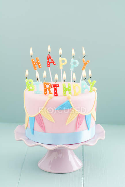 Pastel colors birthday cake, happy birthday burning candles — Stock Photo