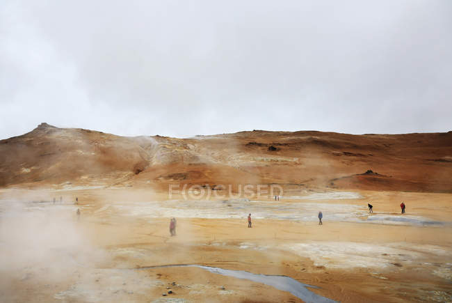 Volcanic  landscape of Iceland, people walking on ground with sulphur steams — Stock Photo