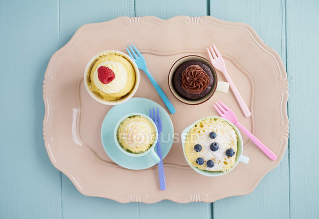 Top view of mug cakes in various cups on tray in pastel colors — Stock Photo