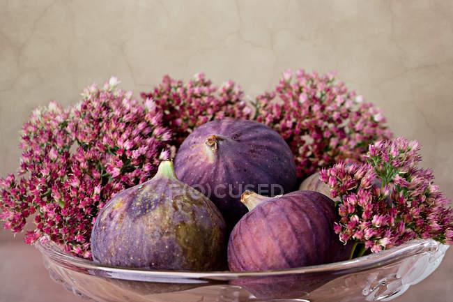 Higos frescos morados exóticos en jarrón de cristal con flores de lirio - foto de stock