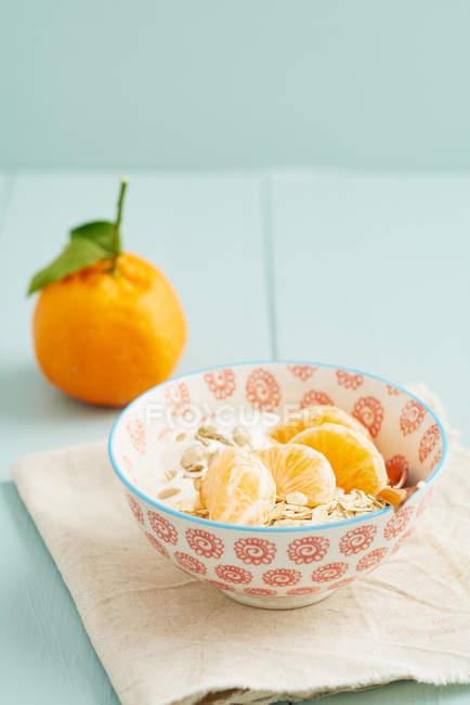 Tazón de fuente con rodajas de mandarinas y cereales, desayuno - foto de stock