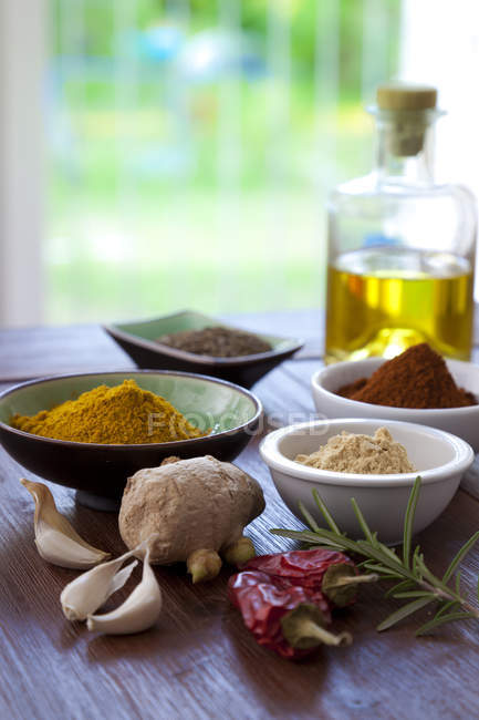 Spices and ingredients on table with oil bottle — Stock Photo