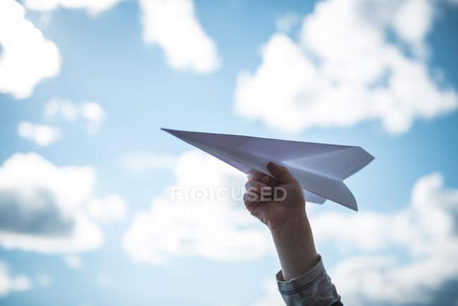 Vista parcial da mão humana segurando o avião de papel contra o céu azul — Fotografia de Stock