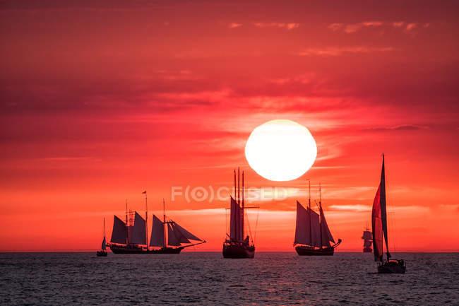 Під час заходу сонця червоне небо з сонцем і Вітрильники плавають у морській воді — стокове фото