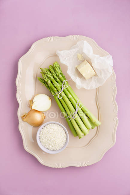 Green asparagus and risotto with onion on tray — Stock Photo