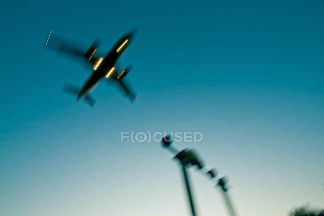 Avião voando no céu azul, movimento borrado, baixo ângulo da noite — Fotografia de Stock