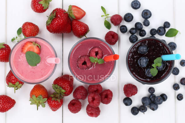 Top view of colorful smoothies with berries and drinking straws — Stock Photo