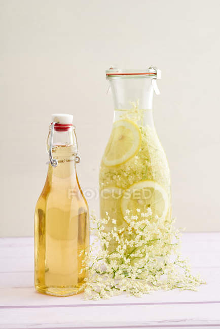 Glass bottles with syrup and lemon slices in lemonade — Stock Photo