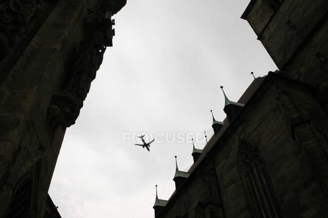 Самолет пролетел в небе выше дома, низкий угол выстрела — стоковое фото
