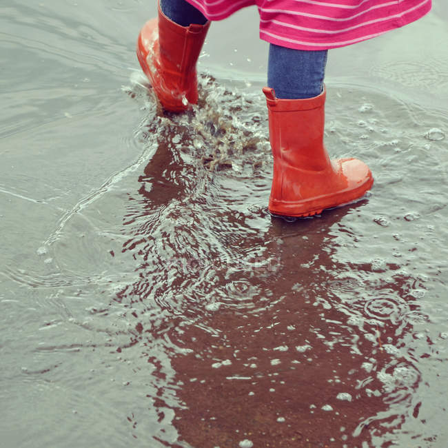 Child walking in rain puddle and wearing red galoshes — Stock Photo