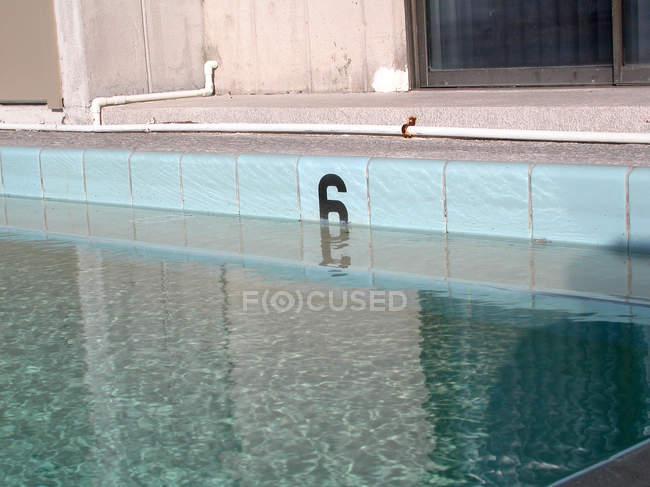 Бассейн с водой и номер шесть плитка стены — стоковое фото