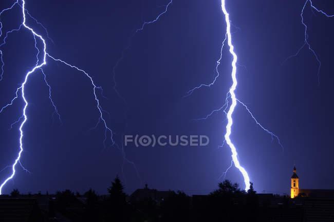 Céu chuvoso azul escuro com relâmpagos e torre da igreja no campo — Fotografia de Stock