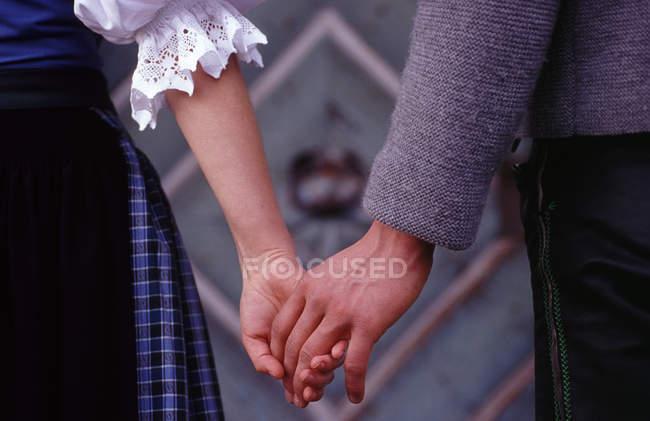 Close up de casal de mãos dadas e vestindo trajes de roupas tradicionais — Fotografia de Stock
