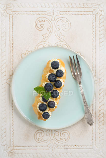 Blue cake plate with eclair and Blueberries — Stock Photo