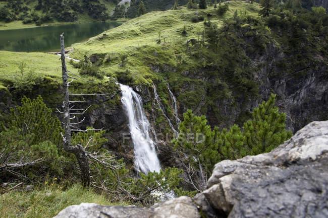 Водопад потоки из зеленого холма — стоковое фото