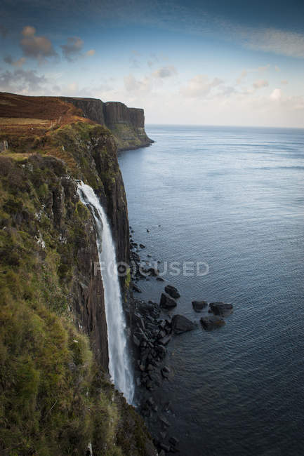 Waterfall flowing from mountains into ocean water — Stock Photo