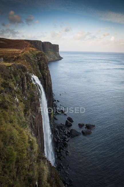 Водопад течет с гор в воды океана — стоковое фото