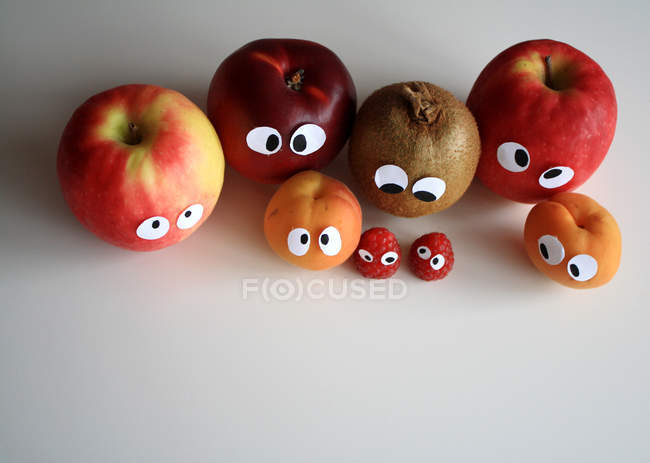 Different fruits with funny cartoon eyes, top view — Stock Photo