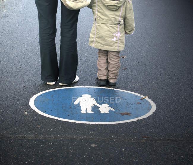 Piétons parent et enfant debout sur le trottoir asphalte au panneau de signalisation rond — Photo de stock