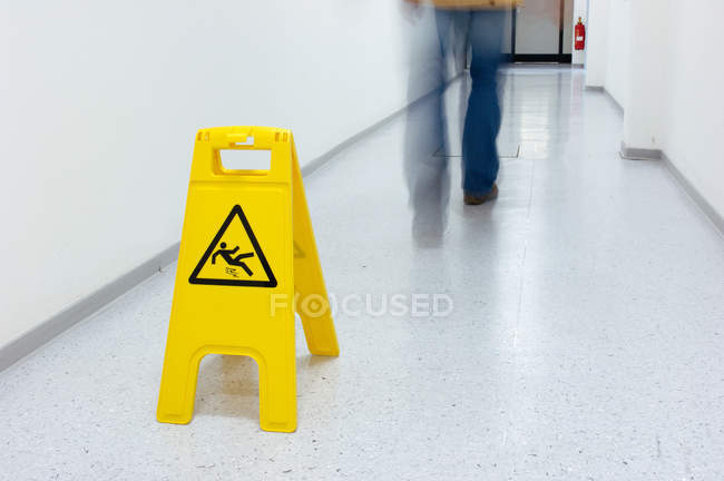 Yellow warning sign of slipping hazard in hallway — Stock Photo