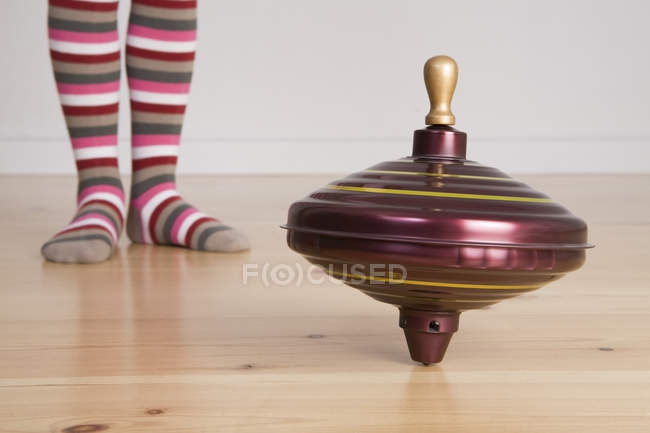 Partial view of little girl standing at spinning top toy — Stock Photo