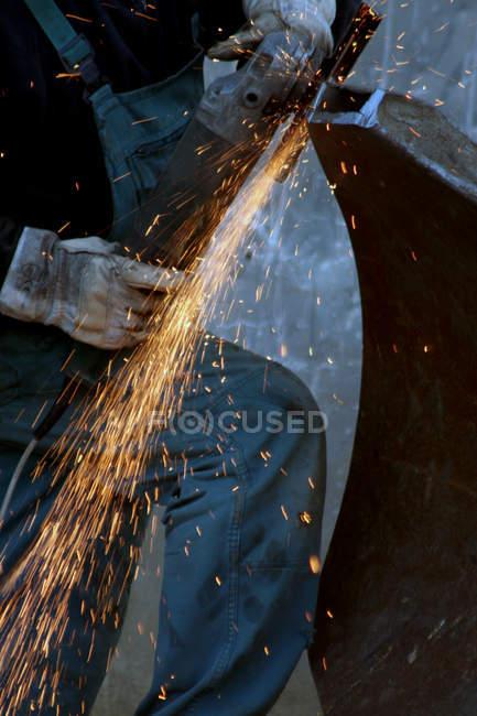 Летающие искры в мастерской, человек, работающий с сталь — стоковое фото