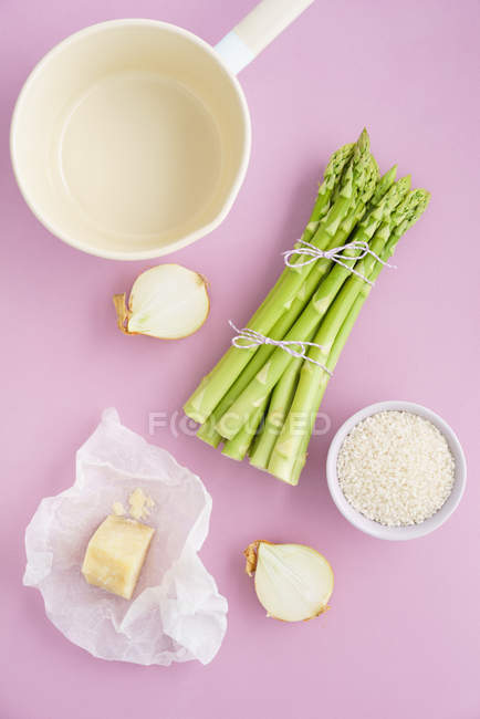 Ingredients on table, green asparagus and risotto — Stock Photo