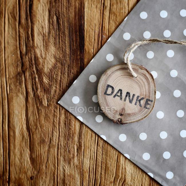 Superficie in legno con tovagliolo e etichetta, danke grazie — Foto stock