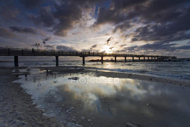 Mer Baltique au coucher du soleil et jetée en bois — Photo de stock