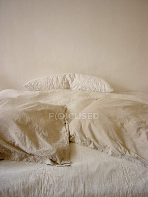 Bed in bedroom, white bedclothes and bed sheets — Stock Photo